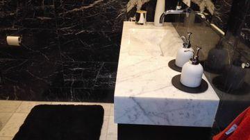 Bianco Carrara stone sink and floor tiles, Nero Marquina walls