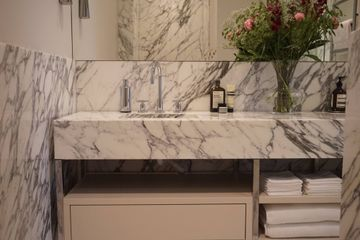 Arabescato marble walls, floors and stone sinks