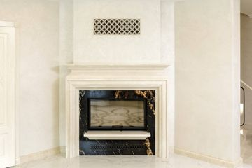 A designer fireplace with Black Fusion granite and Crema Marfil marble